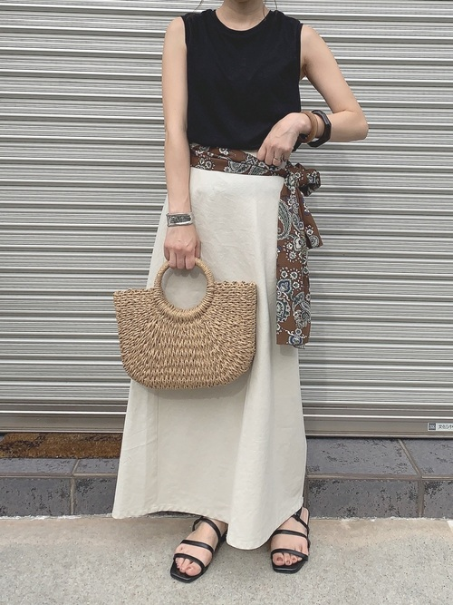 白マーメードロングスカートと黒ノースリーブにペイズリーサッシュスカーフを巻いた女性