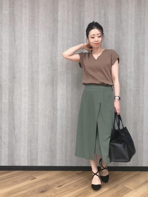茶系ニットカットソーとカーキスリットロングスカートに黒パンプスを履いた女性