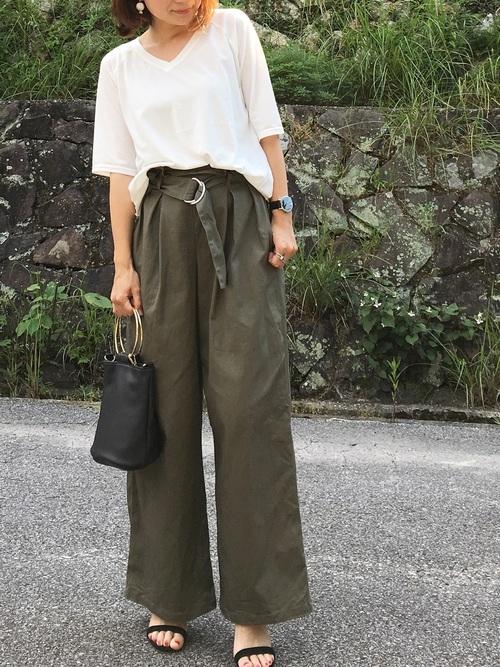 VネックTシャツとカーキワイドパンツにサンダルを履いた女性