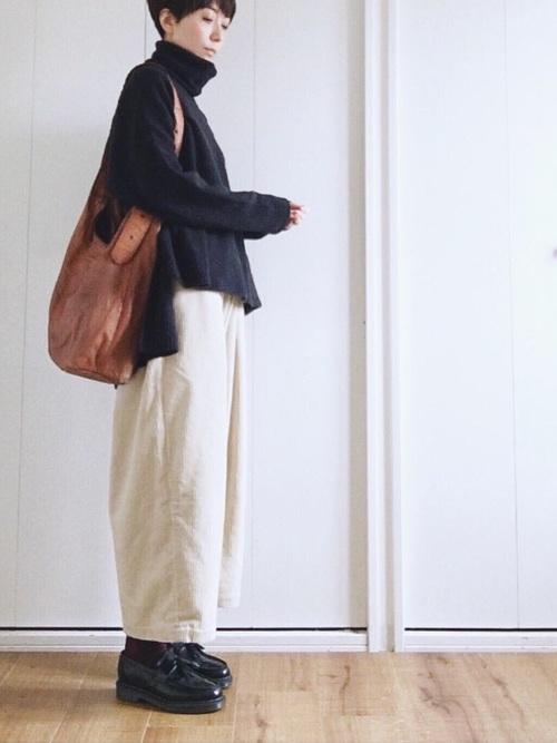 ブラックタッセルローファーとタートルリブニットにコーデュロイワイドパンツを履いた女性