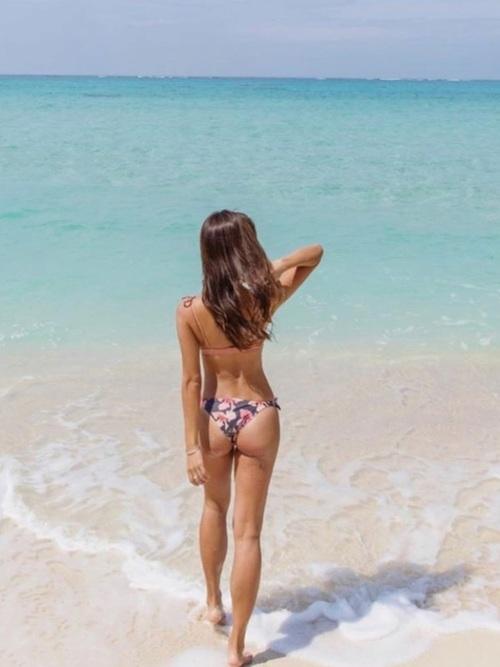 ビキニを着て海で立っている女性