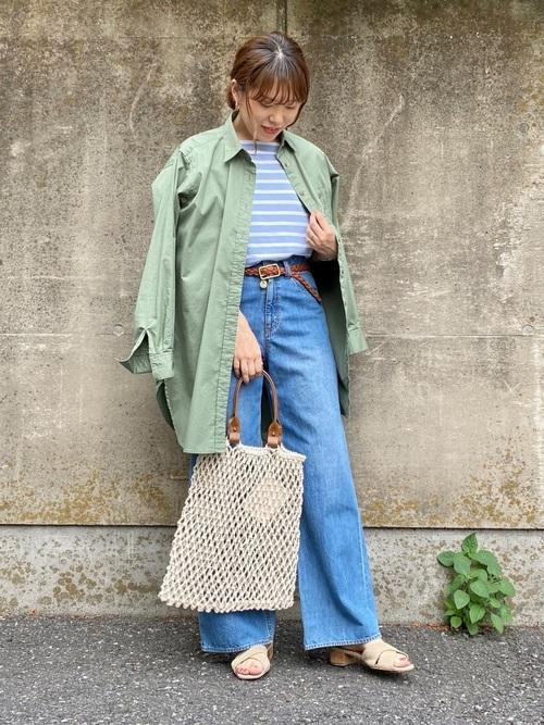 チュニックシャツとボーダーTシャツにデニムワイドパンツを履いた女性