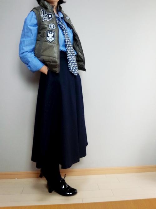 ダウンベストとネクタイにロングスカートを履いた女性