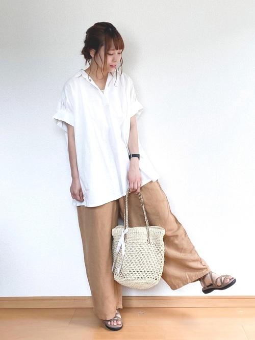 白スキッパーシャツとワイドコクーンパンツにスポーツサンダルを履いた女性