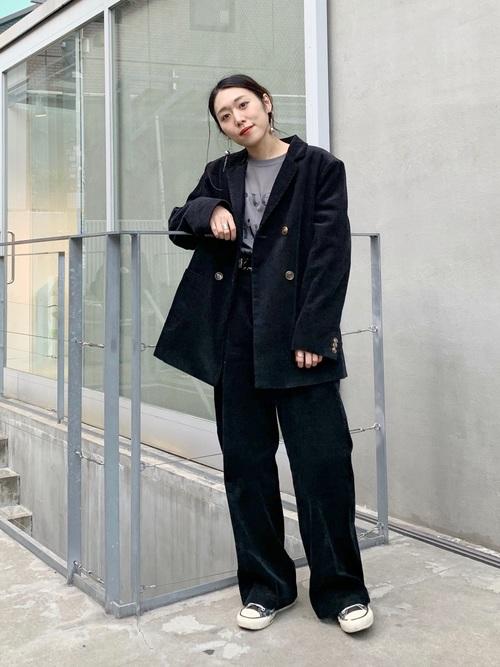 黒コーデュロイジャケットと黒コーデュロイバギーパンツに黒キャンバススニーカーを履いた女性