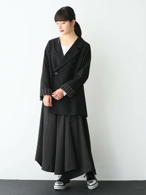 黒アシンメトリーデザインジャケットと白長袖Tシャツにストライプ柄切替えスカートを履いた女性