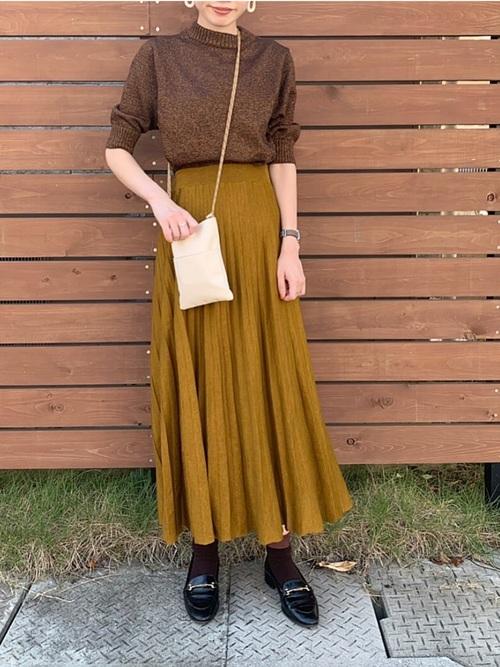 クルーネックニットとロングプリーツスカートにローファーを履いた女性