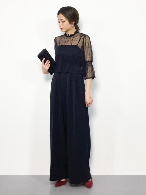 黒キャミサロペットパンツドレスと黒ドットチュールブラウスにボルドーパンプスを履いた女性