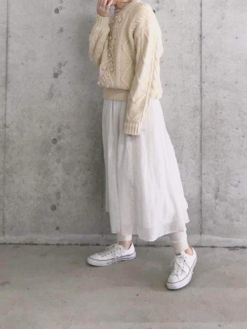 ケーブルニットセーターとロングフレアスカートにレギンスパンツを履いた女性