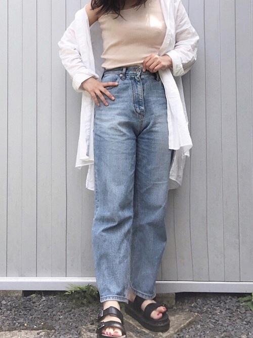 シャツとワンショルダータンクトップにハイウエストストレートデニムパンツを履いた女性