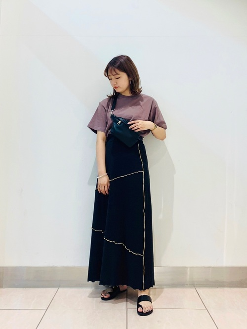 ドロップショルダーTシャツとパイピングデザインロングスカートにボディバッグをもった女性