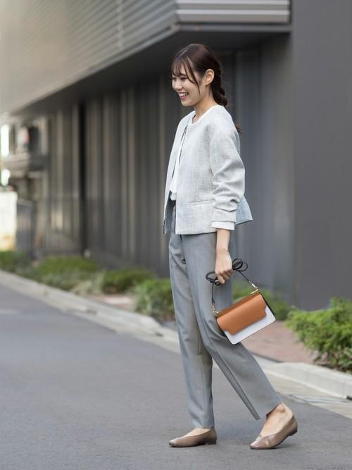 ツイードノーカラージャケットとタックボウタイブラウスにセンタープレスパンツを履いた女性