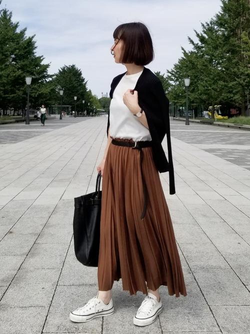 リブVネックカーディガンとコットンノースリーブにマキシ丈プリーツラップスカートを履いた女性