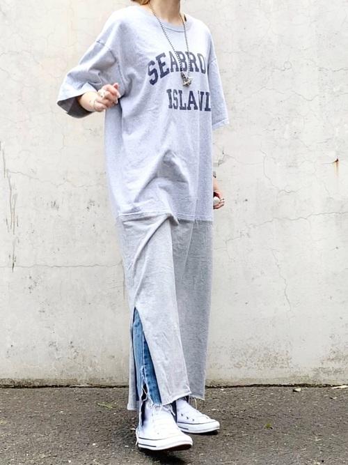 グレーロゴTシャツロングワンピースとスリットデニムパンツに白ハイカットスニーカーを履いた女性
