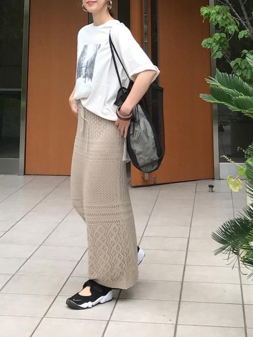 オーバーサイズTシャツとベージュニットロングスカートに黒スニーカーサンダルを履いた女性