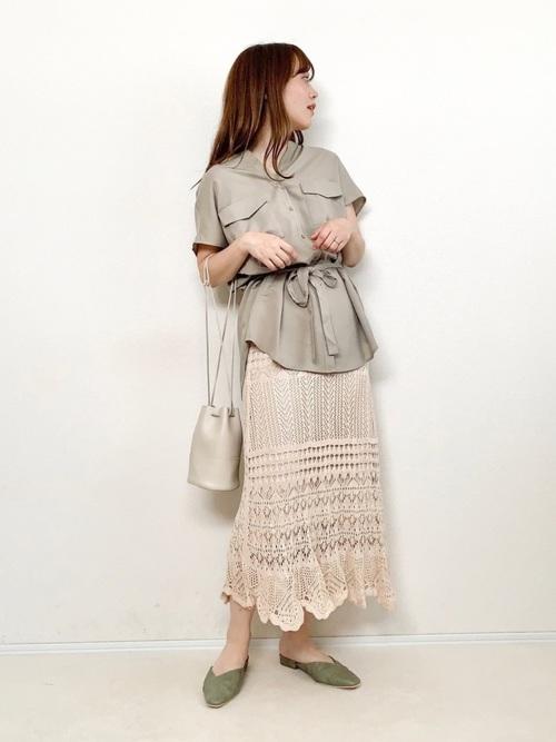 CPOシャツとベージュロングレースニットスカートにVカットフラットミュールを履いた女性