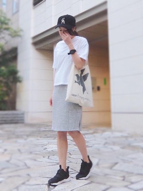 グレースウェットサイドスリットスカートに白5分袖カットソーを着た女性