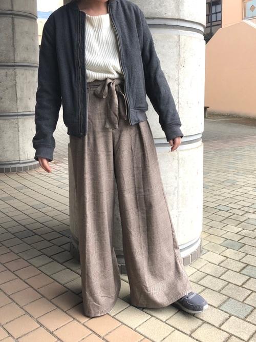 白フェザースリーブプルオーバーにブラウンチェックワイドパンツを履いた女性