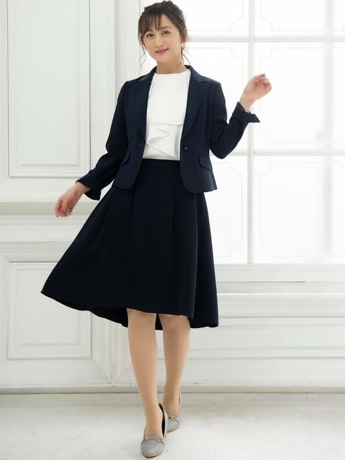 紺ダブルクロステーラードジャケットと白フリルブラウスに紺イレギュラーヘムダブルクロススカートを履いた女性