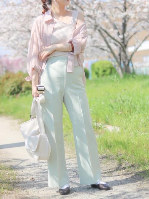 メッセンジャーバッグとシアーシャツにタックパンツを履いた女性