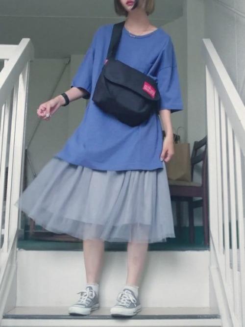 メッセンジャーバッグとビッグシルエットTシャツにチュールスカートを履いた女性