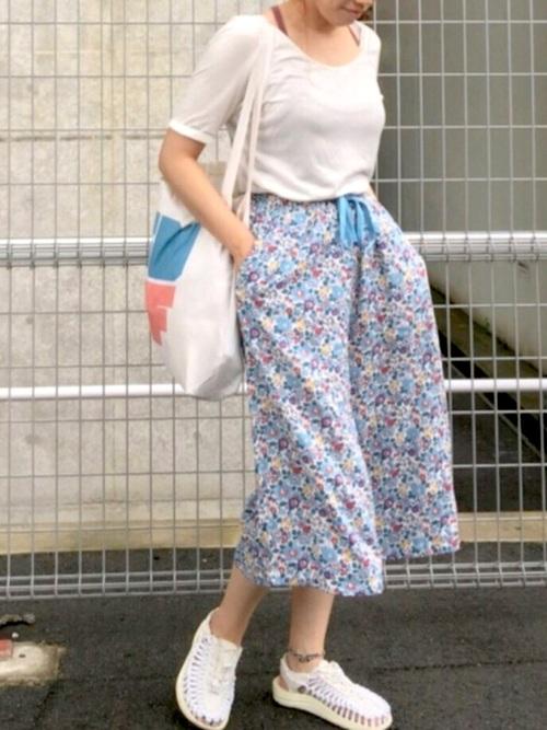 シンプル白Tシャツと【ユニクロ】リラコワイドパンツに白スポーツサンダルを履いた女性