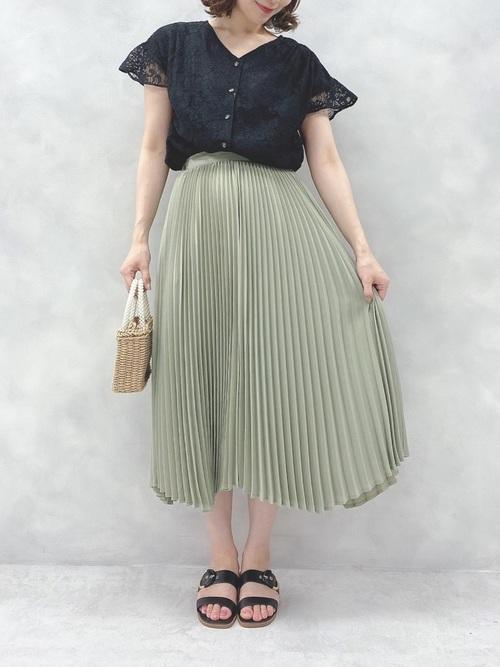 黒レースシャツとグリーンプリーツスカートにブラウンサンダルを履いた女性