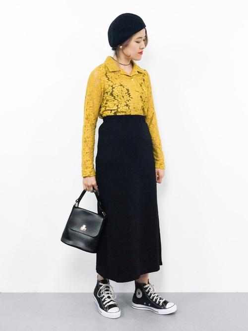 イエローレースシャツと黒セミタイトスカートに黒ハイカットスニーカーを履いた女性