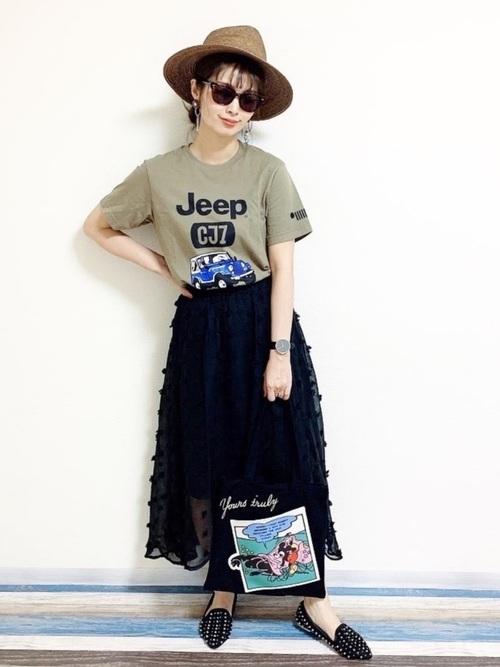 カーキ色のロゴTシャツと黒の透け感あるスカートを合わせ、ディズニーコラボのトートバッグを持ったコーデ