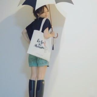 ロングのレインブーツにショートパンツ を合わせる、傘を持った女性