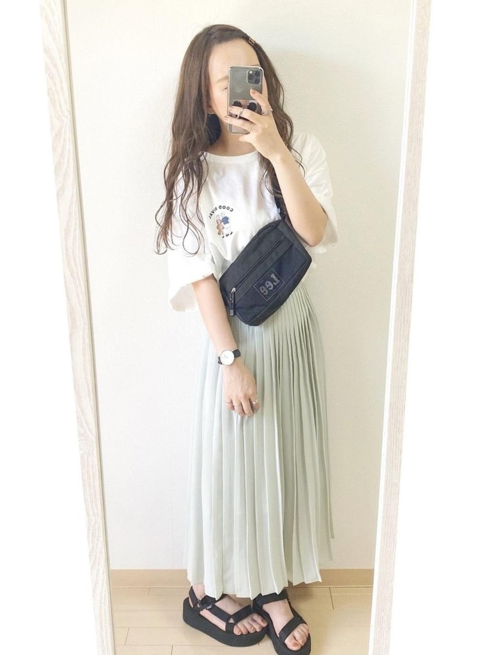白Tシャツとユニクロのグリーンのシフォンプリーツロングスカートを着た女性