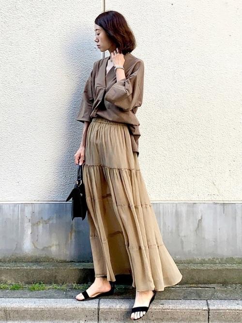 フレアスリーブカットソーにエアリーマキシスカートを穿いた女性