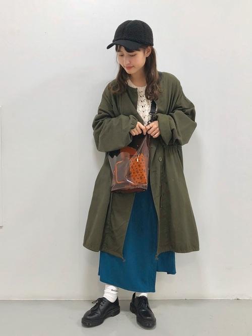 カーキミリタリーコートにラップスカートを履いた女性