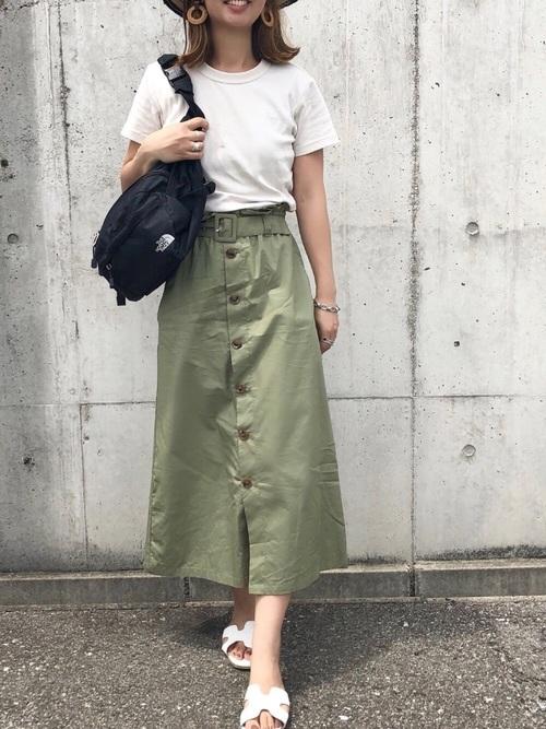 ルーネックTシャツにベルト付きボタンダウンスカートを履いた女性