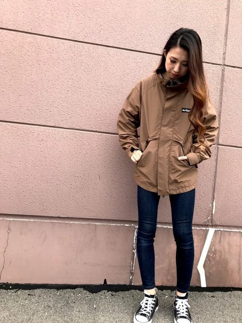 スタンドカラーナイロンジャケットにスキニーデニムパンツを履いた女性