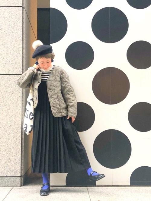 プリーツキャミソールワンピースにキルティングナイロンジャケットを着た女性