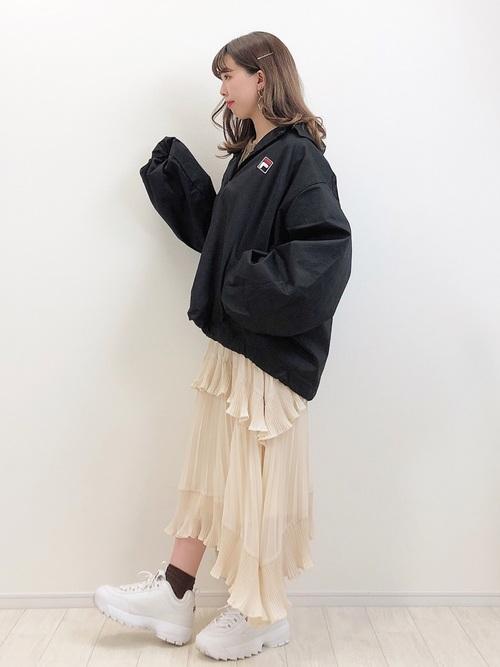 ボリューム袖ナイロンコーチジャケットに二段プリーツロングスカートを履いた女性