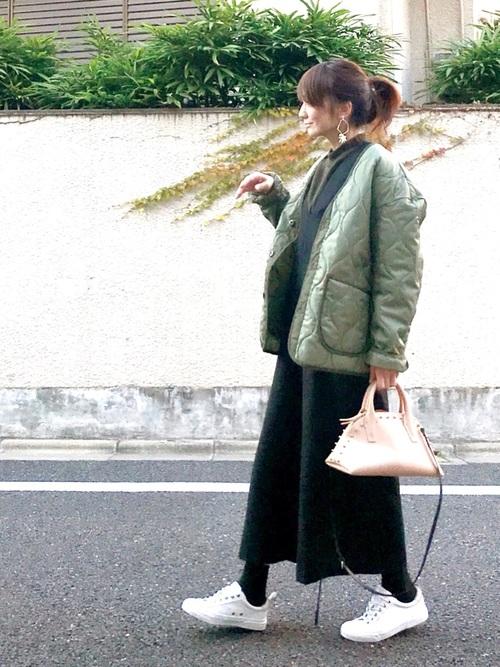 オールインワンにキルティングナイロンジャケットを着た女性