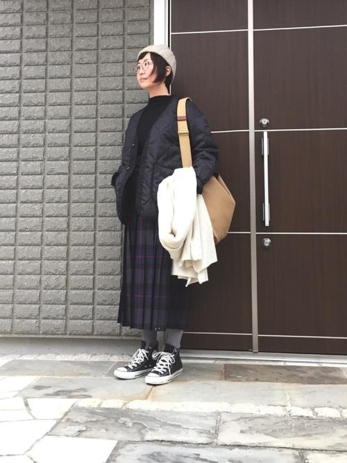 キルティングナイロンジャケットにチェックプリーツスカートを履いた女性