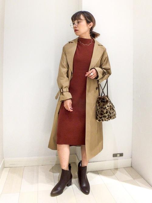 ニットワンピースにロングトレンチコートを着た女性
