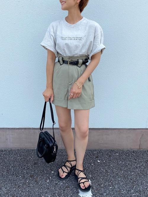 ハイウエストショーパンとオーバーサイズTシャツにコードストラップサンダルを履いた女性