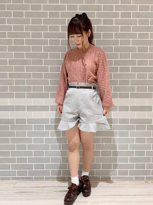 裾フリルショーパンとパールニットにタッセルローファーを履いた女性