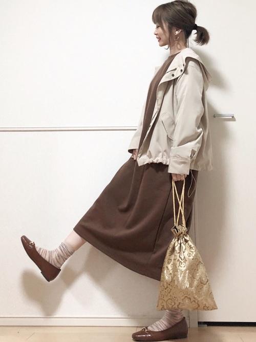 Aラインスウェットワンピとマウンテンパーカーにビットローファーを履いた女性
