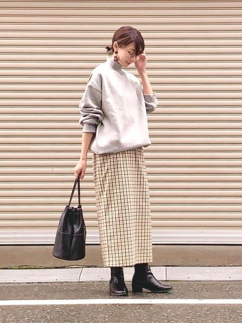ハイネックビッグスウェットとチェックタイトスカートにサイドゴアブーツを履いた女性