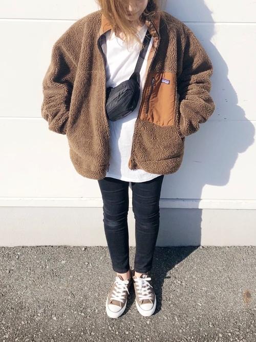 フリースジャケットとオーバーサイズロングTシャツにスキニージーンズを履いた女性
