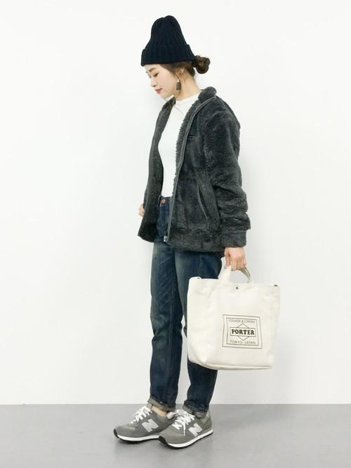 フリースジップアップジャケットとストレートデニムにニット帽を履いた女性