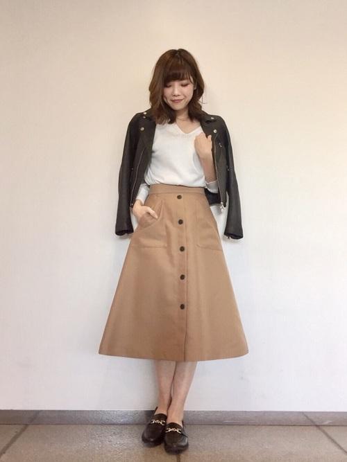 ビットモカシンとダブルライダースジャケットにAラインチノスカートを履いた女性
