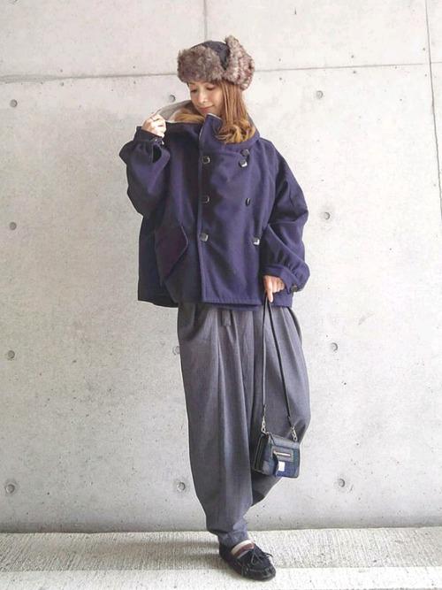 タッセルスエードモカシンシューズとスタンドネックデザインPコートにマスキュリンサルエルパンツを履いた女性
