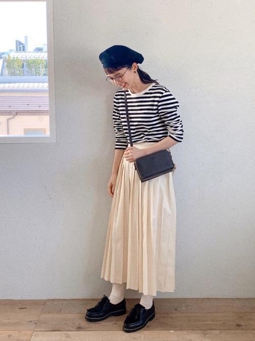 レースアップモカシンとボーダーTシャツにコットンデニムプリーツスカートを履いた女性