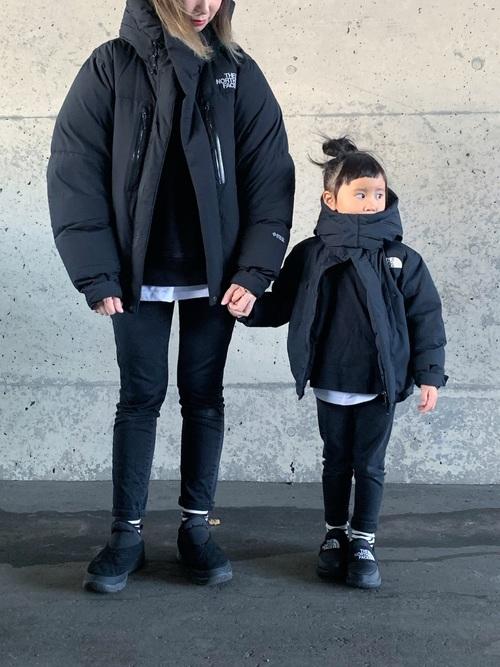 ダウンジャケットとスキニーデニムパンツにスリッポンを履いた女性